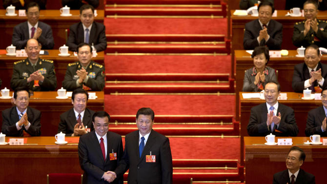 Newly-named Chinese Premier Li Keqiang, front left, poses with newly-named Chinese President Xi Jinping, while former Chinese Premier Wen Jiabao, front row right, claps with delegates and other top Chinese leaders after Li was announced to be the nation's new premier during a plenary session of the National People's Congress held in Beijing's Great Hall of the People Friday, March 15, 2013. (AP Photo/Alexander F. Yuan)