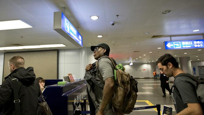 Former NBA star Dennis Rodman, center, walks to the check in counter at the departure hall of Beijing Capital International Airport in Beijing Tuesday, Feb. 26, 2013. Rodman, three members of the Harlem Globetrotters basketball team, a VICE correspondent and a production crew from the company are visiting North Korea to shoot footage for a new TV show set to air on HBO in early April, VICE told The Associated Press in an exclusive interview before the group's departure from Beijing. (AP Photo/Andy Wong)