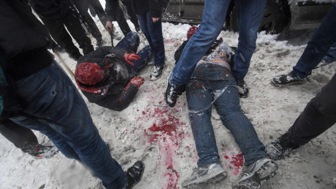 In this photo taken on Friday, March 15, 2013, members of a pro-Kremlin youth group douse with red paint two tied-up pushers of spice, a synthetic drug, in Moscow, Russia. Russian officials and anti-drugs campaigners say that spice has become one of the most dangerous drugs widely available to youngsters and almost impossible to ban because of the constantly changing chemical ingredients. (AP Photo/Alexander Zemlianichenko Jr)