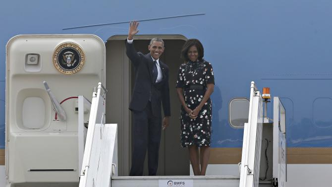 U.S. President Obama waves from the steps of Air Force One as the first lady Michelle watches upon their departure at the airport in New Delhi