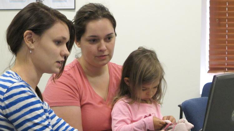 Debora Costa right, tries to sign up for insurance coverage for her two children, including 2-year-old Victoria, Wednesday, Oct. 2, 2013, with help from Champaign Urbana Public Health District employee Alice Cronenberg in Champaign, Ill. Costa, who recently moved to Illinois from Brazil with her graduate-student husband and children, found after about 10 minutes that she didn't have all the information she would need to sign up. (AP Photo/David Mercer)
