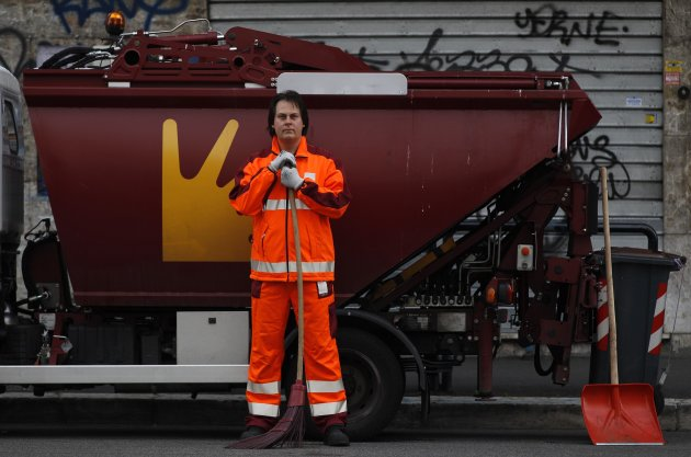 Francesco Foglia, 37, poses for a picture as he works as a street sweeper in downtown Rome