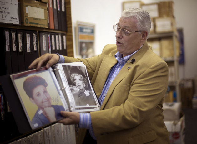 In this Friday, Oct. 19, 2012 photo, memorabilia collector Ken Kallin shows off autographed photos of Ann B. Davis, left, and Betty Davis, at his Oakland Park, Fla. office. Three decades ago, Kallin b