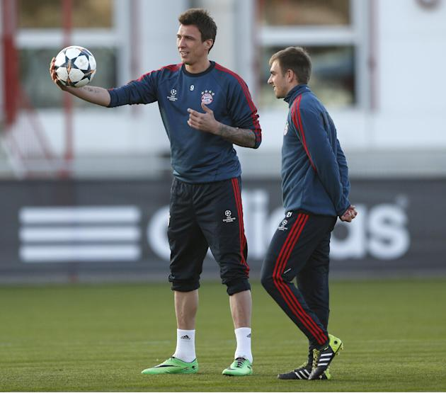Bayern's Mario Mandzukic of Croatia, left, and team captain Philipp Lahm wait for the start of a training session in Munich, southern Germany, Monday, March 10, 2014, ahead of their round of 16 se