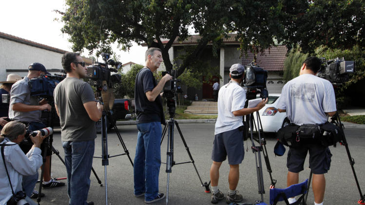 "News media gather outside the home of Nakoula Basseley Nakoula in Cerritos, Calif. Thursday , Sept. 13, 2012.  Federal authorities had concluded that Nakoula Basseley Nakoula, 55, was behind ""Innocence of Muslims,"" a film that denigrated Islam and the prophet Muhammad and sparked protests earlier this week in Egypt, Libya and most recently in Yemen.  (AP Photo/Nick Ut)"