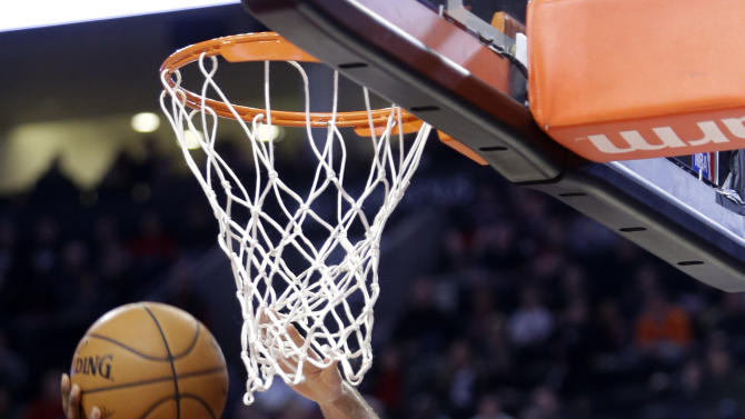 New York Knicks guard Tim Hardaway Jr., left, goes for a reverse layup against Portland Trail Blazers forward Joel Freeland, from England, during the first half of an NBA basketball game in Portland, Ore., Sunday, Dec. 28, 2014.(AP Photo/Don Ryan)