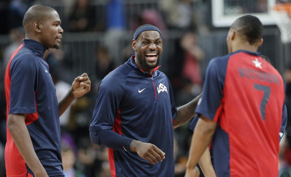 USA's Lebron James, center, jokes with teammates Kevin Durant, left, and Russell Westbrook, right, a preliminary men's basketball game agaisnt Tunisia at the 2012 Summer Olympics, Tuesday, July 31, 2012, in London. (AP Photo/Eric Gay)