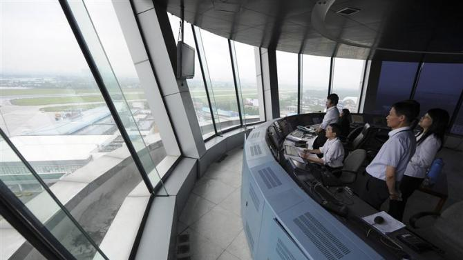 Employees look out from a control tower of Hefei Luogang Airport in Hefei