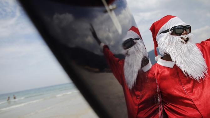 Carlos Bahia, dressed as Santa Claus, waves to people at the Maresias beach, in the state of Sao Paulo