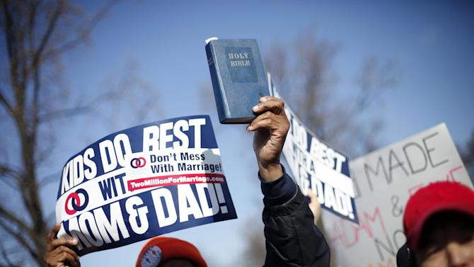 FILE - In this March 26, 2013, file photo a demonstrator holds up bible while marching outside the Supreme Court in Washington during the court's hearing of arguments on California's voter approved ban on same-sex marriage, Proposition 8. Sometime this early July, the Court will announce the outcomes in cases on Proposition 8, and the federal Defense of Marriage Act, the federal law defines marriage as the union of a man and a woman. (AP Photo/Pablo Martinez Monsivais, File)