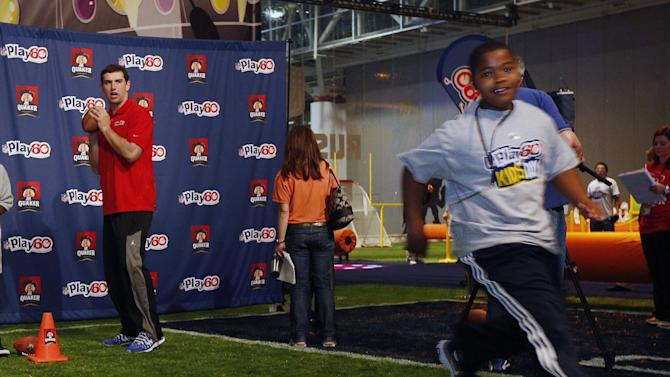 IMAGE DISTRIBUTED FOR QUAKER OATS - NFL Quarterback and Quaker spokesperson Andrew Luck runs football drills with New Orleans kids at Ernest N. Morial Convention Center at Kid's Day at NFL Experience Driven by GMC in New Orleans Wednesday, Jan. 30, 2013.  Luck serves as healthy living role model and encourages kids to eat right and stay active. (Jonathan Bachman/AP Images for Quaker Oats)