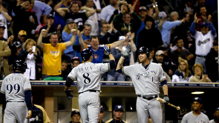 Milwaukee Brewers' Ryan Braun is congratulated by Corey Hart as Brewers fans celebrate after his third home run against the San Diego Padres in the seventh inning of a baseball game Monday, April 30, 2012 in San Diego. (AP Photo/Lenny Ignelzi)