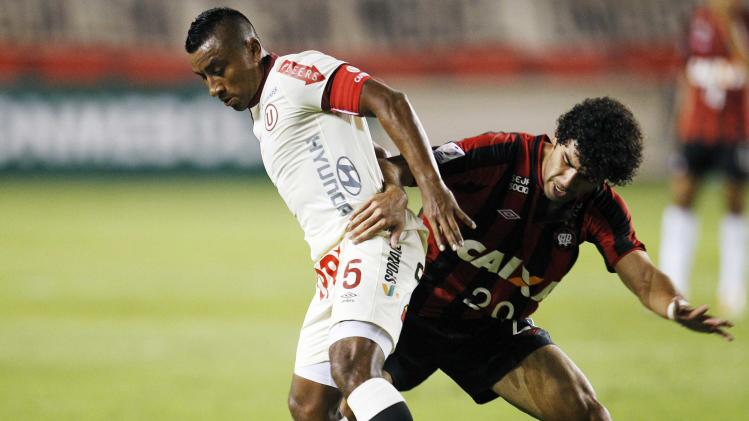 Mendes of Brazil's Atletico Paranaense fights for the ball with Gonzales of Peru's Universitario during their Copa Libertadores soccer match in Lima