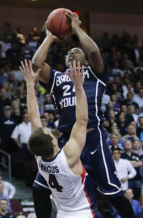 Gonzaga's Kevin Pangos (4) draws an offensive foul on BYU's Frank Bartley IV as Bartley shoots during the second half of an NCAA college basketball game for the West Coast Conference men's