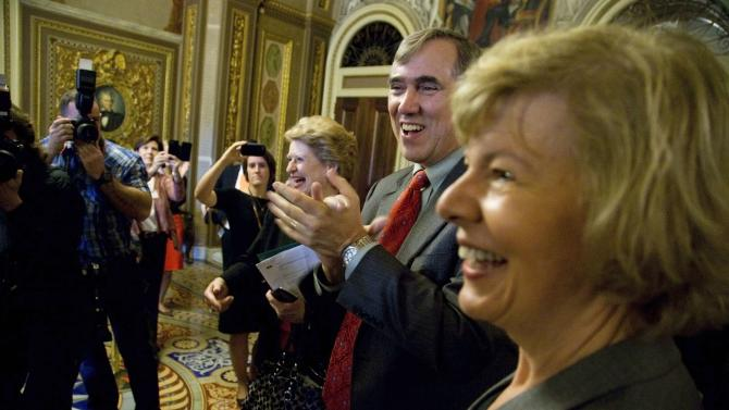 Merkley and Baldwin celebrate with supporters after a vote to pass the ENDA legislation to ban workplace discrimination against gays, at the U.S. Capitol in Washington