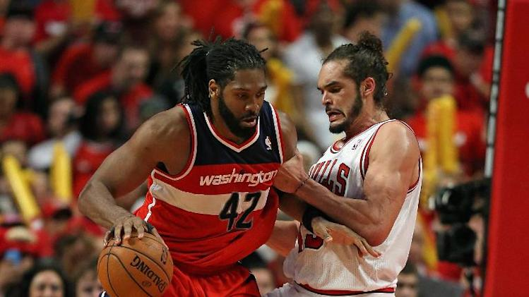 Nene (L) of the Washington Wizards moves past Joakim Noah of the Chicago Bulls in Game 1 of their Eastern Conference quarter-finals during the 2014 NBA Playoffs, at the United Center in Chicago, Illinois, on April 20, 2014