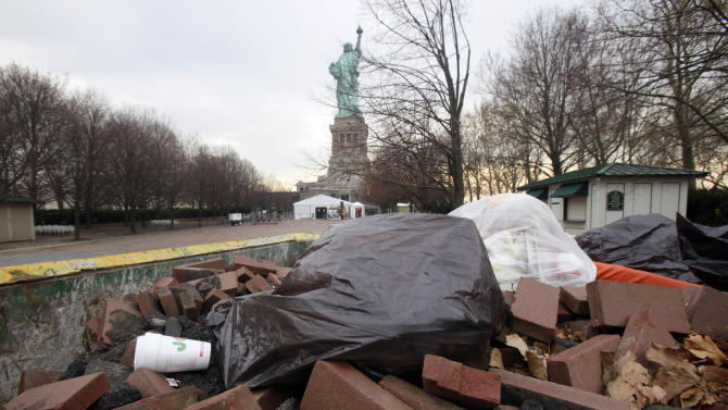 Bricks from the walkway that surrounds Liberty Island are collected in a Dumpster, in New York,  Friday, Nov. 30, 2012. Tourists in New York will miss out for a while on one of the hallmarks of a visit to New York, seeing the Statue of Liberty up close. Though the statue itself survived Superstorm Sandy intact, damage to buildings and Liberty Island's power and heating systems means the island will remain closed for now, and authorities don't have an estimate on when it will reopen. (AP Photo/Richard Drew)
