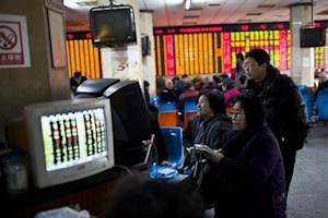 Investors look at computer screens showing stock information at a brokerage house in Shanghai, March 4, 2014. REUTERS/Aly Song