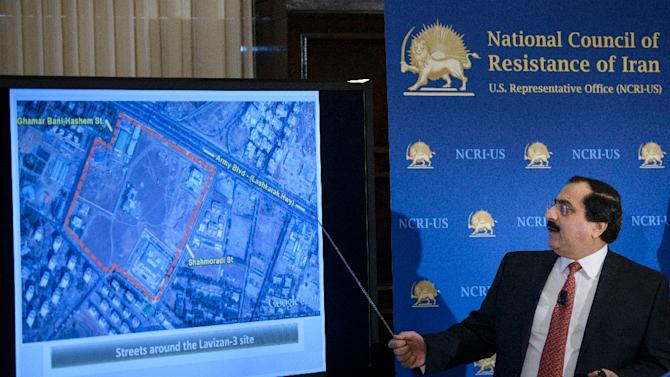 Alireza Jafarzadeh, deputy director of the Washington office of the National Council of Resistance of Iran, shows satellite photos during a press conference at the National Press Club February 24, 2015 in Washington, DC