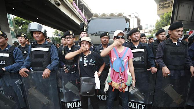 "Two protesters, center, gesture in front of line of Thai riot police officers during an anti-coup demonstration at the Victory Monument in Bangkok, Thailand Monday, May 26, 2014. Bolstered by a royal endorsement Monday to run the country after last week's coup, Thailand's junta leader warned citizens not to cause trouble, not to criticize, not to protest, or else face a return to the ""old days"" of street violence. (AP Photo/Wason Wanichakorn)"