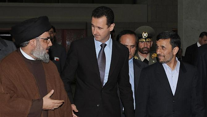 "FILE -- In this Thursday February 25, 2010 file photo, released by the Syrian official news agency SANA, Hezbollah leader sheik Hassan Nasrallah, left, speaks with Syrian President Bashar Assad, center, and Iranian President Mahmoud Ahmadinejad, right, upon their arrival for a dinner, in Damascus, Syria. The powerful alliance of Iran, Syria and militant groups Hezbollah and Hamas, once dubbed the ""Axis of Resistance,"" is fraying. Iran's economy shows signs of distress from nuclear sanctions, Syria's president is fighting for his survival, Hezbollah is under fire by Lebanese who blame it for the assassination of an anti-Syrian intelligence official and Hamas _ the Palestinian arm _ has bolted. (AP Photo/SANA, File)"