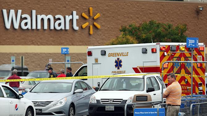 An ambulance sits in the parking lot of a Wal-mart on Friday, June 21, 2013 in Greenville, N.C. A man armed with a shotgun wounded one person at a North Carolina law firm Friday before crossing a busy street and entering a Wal-Mart, where he shot three more people before officers subdued him, police said. Greenville Police Chief Hassan Aden said the suspect was shot by officers at the entrance of the store. He didn't have the conditions of those shot and didn't have a motive. (AP Photo/The Daily Reflector, Aileen Devlin)