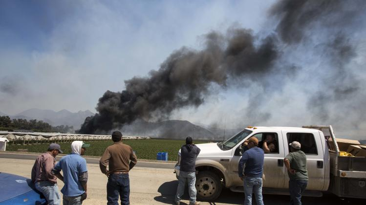 Farm workers watch as smoke rises from chemical storage tanks near a strawberry farm in Camarillo, Calif., Thursday, May 2, 2013. (AP Photo/Ringo H.W. Chiu)