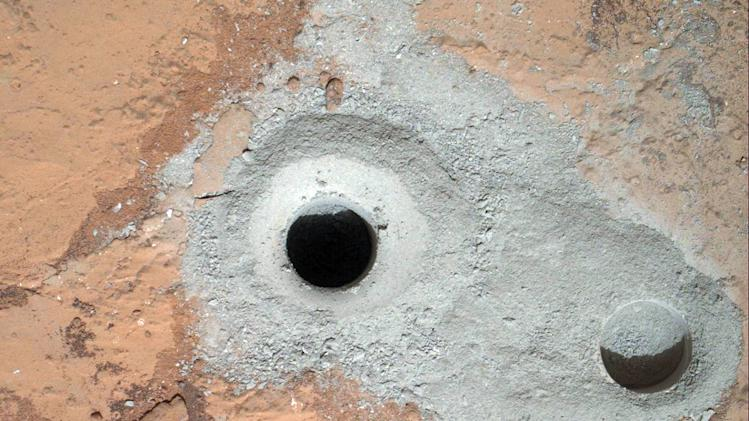 This image released by NASA on Saturday Feb. 9, 2013 shows a fresh drill hole, center, made by the Curiosity rover on Friday, Feb. 8, 2013 next to an earlier test hole. Curiosity has completed its first drill into a Martian rock, a huge milestone since landing in an ancient crater in August 2012. (AP Photo/NASA)