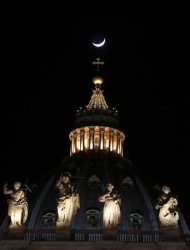 The moon, approaching the first quarter, is seen over the dome of Saint Peter&#39;s Basilica at the Vatican March 15, 2013. REUTERS/Chris Helgren
