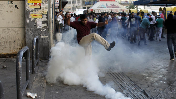 A man tries to kick a tear-gas canister away, as Muslims protest against a film produced in the U.S. that they say insults the Prophet Muhammad, in Athens, Sun. 23, 2012.  The protesters tried to march to the U.S. Embassy, but riot police blocked all exits from the square and used tear gas to disperse the protesters. It is the first such protest against the film by Muslims in Greece.(AP Photo/Kostas Tsironis)