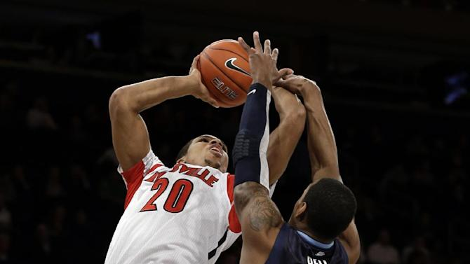 This photo taken March 14, 2013 shows Louisville's Wayne Blackshear (20) shooting over Villanova's James Bell (32) during the first half of an NCAA college basketball game at the Big East Conference tournament in New York.  The Cardinals have shown that they're comfortable being front-runners in their season-long quest to go further than last year's Final Four appearance. Now, they enter the NCAA tournament as the overall No 1 seed. (AP Photo/Frank Franklin II)