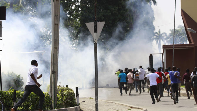 Policemen fire teargas on protesting students of university of Lagos, following the renaming of their school in Lagos, Nigeria, Friday, June 1, 2012. Police in Nigeria's largest city used tear gas Friday to try to disperse a crowd of several hundred university students angry at the president's decision to change the name of their school. (AP Photo/Sunday Alamba)