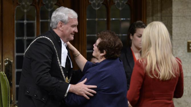 Conservative MP Tilly O'Neill Gordon hugs Sergeant-at-Arms Kevin Vickers as Eve Adams lines up to pay her respects following speeches by leaders in the House of Commons Thursday, Oct. 23, 2014 in Ottawa. Vickers was among those who opened fire on Michael Zehaf Bibeau, who stormed Parliament Hill on Wednesday. (AP Photo/The Canadian Press, Adrian Wyld)