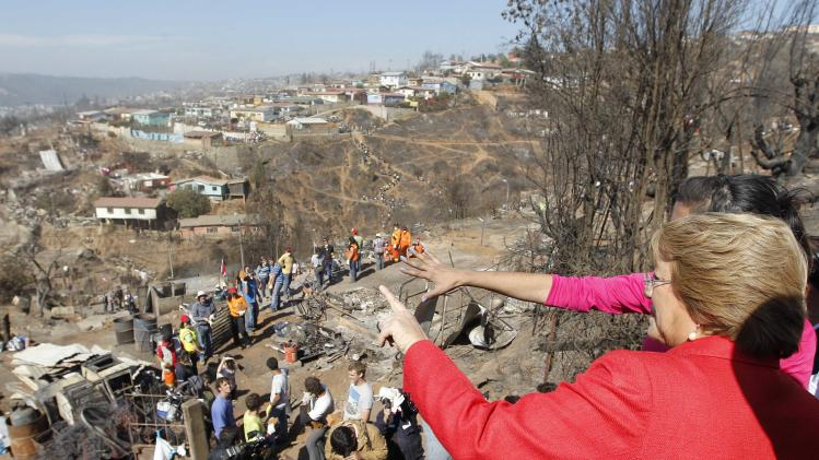 Chilean President Michelle Bachelet look at part of a large area destroyed after a fire burned several neighbourhoods in the hills in Valparaiso city,