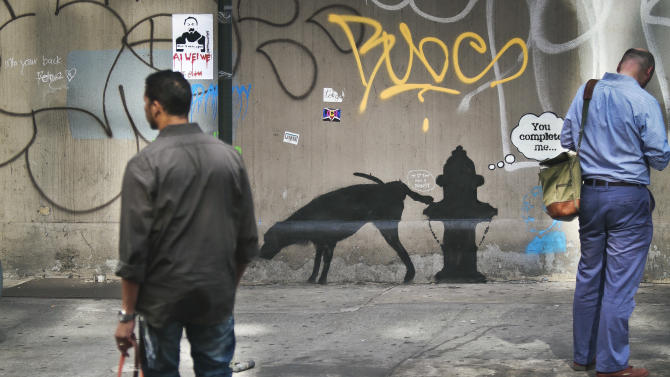 "Graffiti by the secretive British artist Banksy, featuring a dog and a fire plug, draws attention on 24th Street, near Sixth Avenue in New York, on Friday, Oct. 4, 2013. Banksy graffiti is turning up on the streets of the city and all over social media. Banksy announced on his website that he is undertaking ""an artists residency on the streets of New York"" this month. (AP Photo/Bebeto Matthews)"