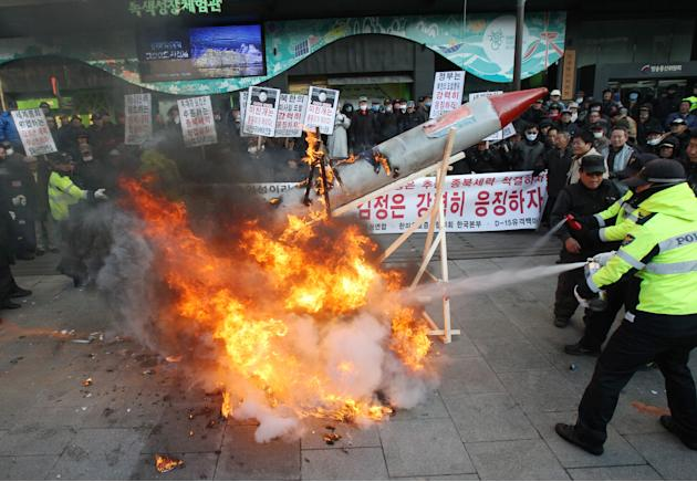 South Korean protesters burn a mock rocket as police officers spray fire extinguishers during a rally denouncing North Korea's rocket launch in Seoul, South Korea, Wednesday, Dec. 12, 2012.  North Kor