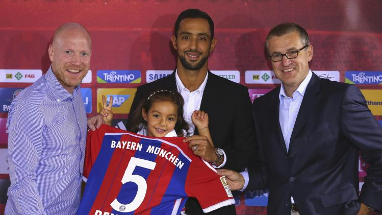 Bayern Munich's new player Benatia poses with his daughter Lina, club's sporting director Sammer and CFO Dreesen after a news conference at Bayern Munich's headquarters in Munich