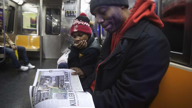Daniel Mitchell talks with son about death of two police officers who were shot in Brooklyn borough, as they read local paper on G train in New York