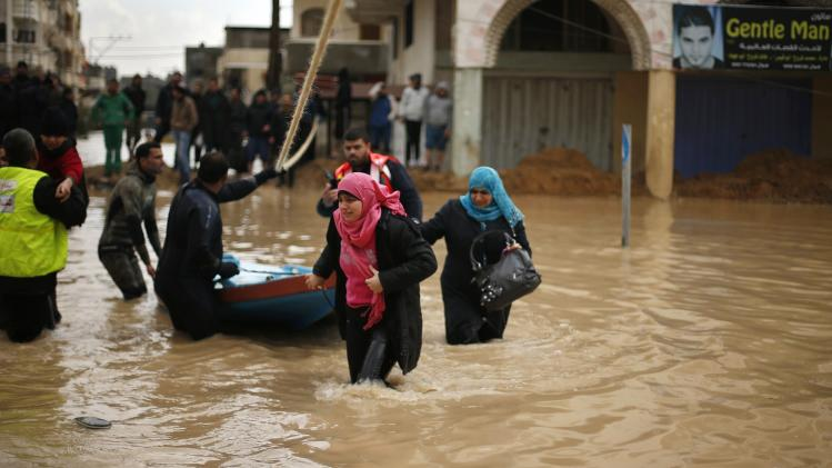 Members of the Palestinian civil defense evacuate people after their houses were flooded with rainwater on a stormy day in Gaza City