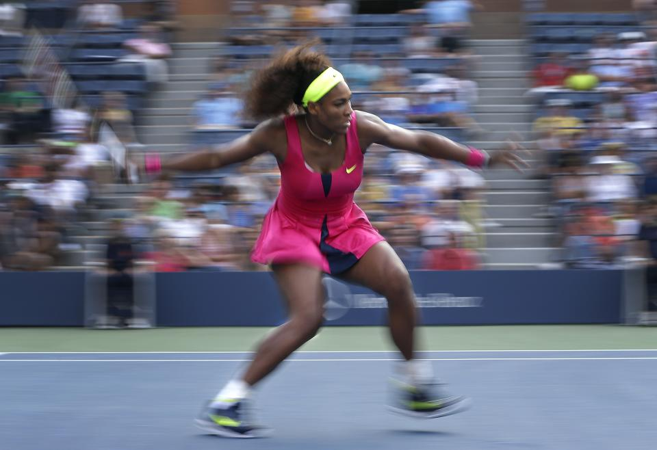 In this photograph made with a slow shutter speed, Serena Williams returns a shot to  Spain's Maria Jose Martinez Sanchez in the second round of play at the 2012 US Open tennis tournament,  Thursday, Aug. 30, 2012, in New York. (AP Photo/Darron Cummings)