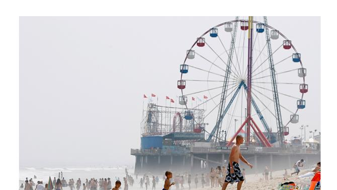 FILE - In this combination of two file photos, the Funtime Pier in Seaside Heights, N.J. is shown before and after Superstorm Sandy made landfall on the Jersey Shore. At top in this Aug. 10, 2010 file photo, the Funtime Pier rises from the sand and surf at Seaside Heights on the New Jersey coast. Below, Funtime Pier Owner Billy Major surveys the damage on Wednesday, Oct. 31, 2012 after Sandy tore through the region and left only four rides standing. Humans have an affinity for water. But in these recent jumbled days, the collapsed houses, flooded subway tunnels and washed-out roads left in Sandy's wake remind us once again: Our deep-seated human desire to be near the water _ to be attracted and comforted by it, to build alongside it and crave its attractions _ has an undeniable dark side. Top (AP Photo/Mel Evans) Bottom (AP Photo/Star-Ledger, David Gard, Pool)