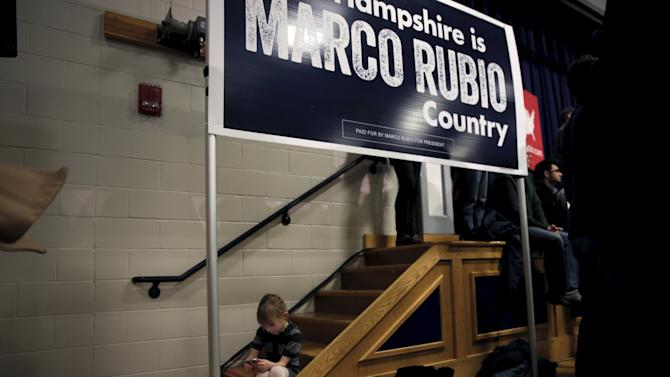 A girl plays on a mobile phone as U.S. Republican presidential candidate Marco Rubio speaks at a town hall campaign rally in Derry,