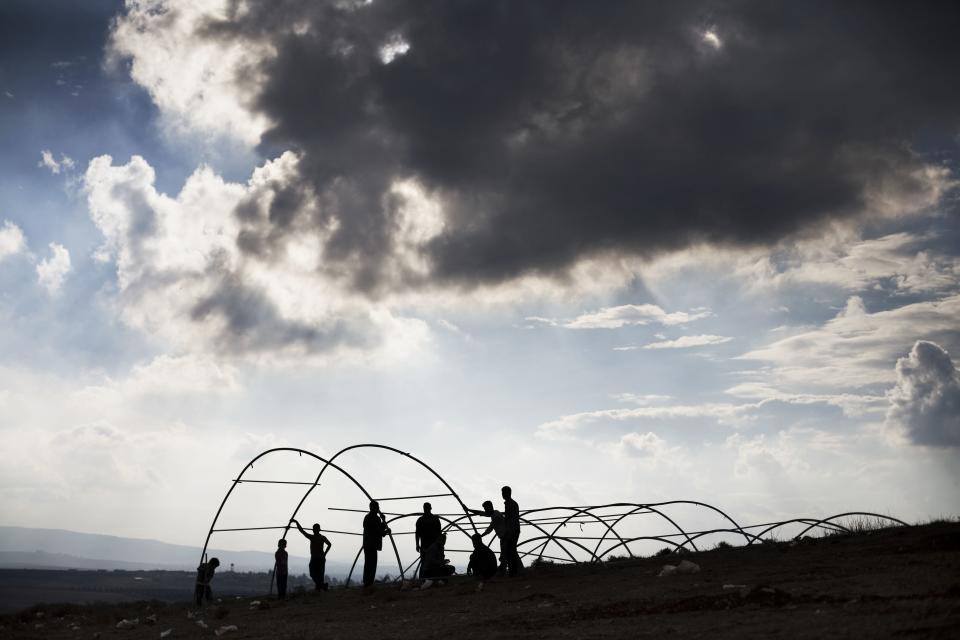 Syrian displaced men build a tent in a refugee camp near  Atma, Idlib province, Syria, Friday, Oct. 26, 2012. A powerful car bomb exploded in Damascus and scattered fighting broke out in several areas across Syria Friday, quickly dashing any hopes that a shaky holiday cease-fire would hold for four days.(AP Photo/ Manu Brabo)
