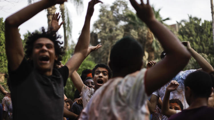 "In this Saturday, April 6, 2013 photo, Egyptian youths dance during a ""Mahraganat"" Arabic word for ""festivals,"" concert by music singers, in Cairo, Egypt. A new musical sound emerged from the underground in Egypt since the country's 2011 revolution, a rapid-fire electronic beat, mixed with hypnotic rhythms drawn from religious festivals and fired up with auto-tuned vocals. Besides getting club crowds dancing all night long, it has given a rebellious voice to long marginalized youth, telling stories of everyday life in beaten-down neighborhoods of Cairo. (AP Photo/Nariman El-Mofty)"