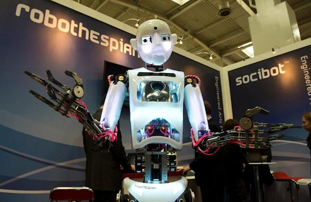 "The lifesize humanoid robot ""RoboThespian"" interacts with visitors to the Engineered Arts stand at CeBIT on March 11, 2014 in Hanover, central Germany"