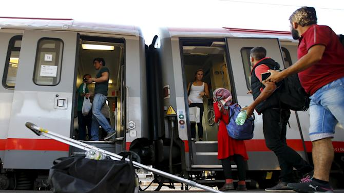 Travellers believed to be migrants coming from Hungary enter a train to Germany at the railway station in Vienna
