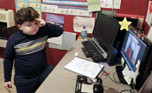 In this Tuesday, Jan. 22, 2013 photo, Devon Carrow stands for the Pledge of Allegiance while attending school from home while operating a robot in the classroom, in Orchard Park N.Y. Carrow's life-thr