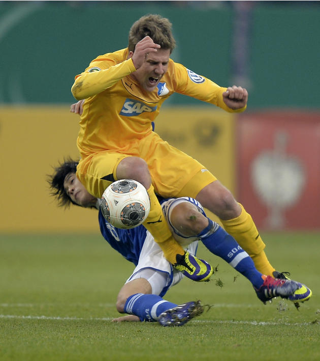 Hoffenheim's Sven Schipplock, up, falls on Schalke's Atsuto Uchida during the German soccer cup third round match between FC Schalke 04 and TSG Hoffenheim in Gelsenkirchen, Germany, Tuesday, D