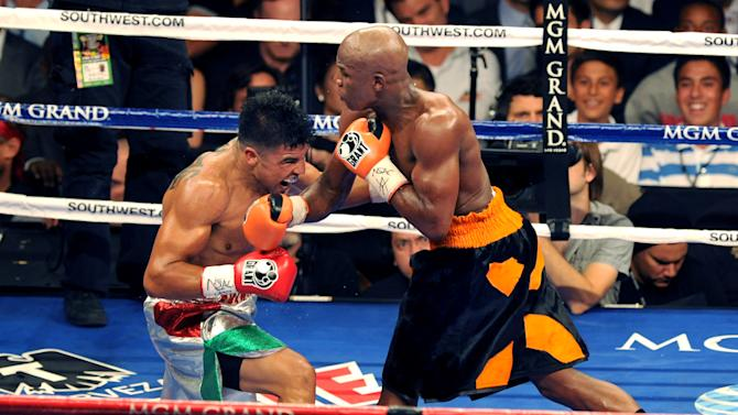 In this photo provided by the Las Vegas News Bureau, Victor Ortiz, left, battles Floyd Mayweather Jr. for the WBC welterweight championship title, Saturday, Sept. 17, 2011, in Las Vegas. (AP Photo/Las Vegas News Bureau, Brian Jones)