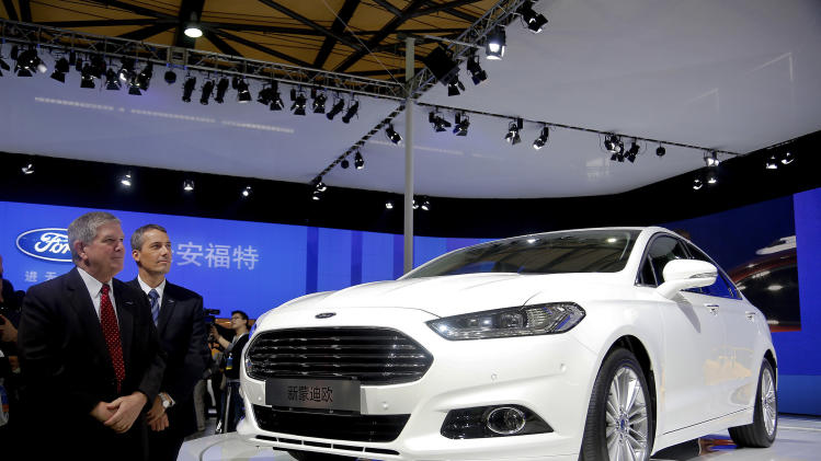 Officials from Ford Motor Co. stand near the new Ford Mondeo model after they unveiled the car at the Shanghai International Automobile Industry Exhibition (AUTO Shanghai) media day in Shanghai Saturday, April 20, 2013. (AP Photo)